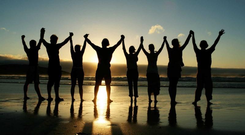 Pessoas de mãos dadas na praia